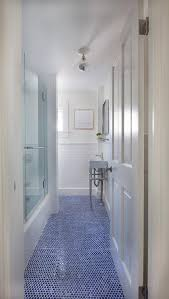 long white bathroom with blue hexagon tile floor