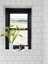 A tiled windowsill becomes a clever, water-resistant shelf for everyday  items and display. The black window frame makes white accessories pop.