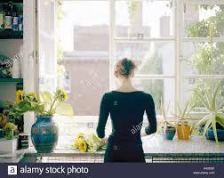 Küche Fensterbank Frau Sonnenblumen Vase Rückansicht Hausfrau