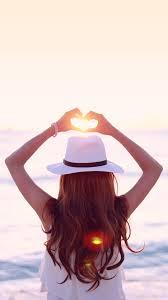 オシャレなiphone壁紙海に落ちていく夕陽にハートの手をかざす女の子
