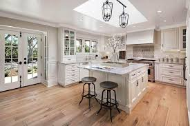 light hickory hardwood floor with swivel bar stools under marble overhang and skylight over glass lantern