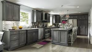 gray oak kitchen cabinets granite countertop black beige purple rug side by side refrigerator wood flooring gas range and hood tile backsplash
