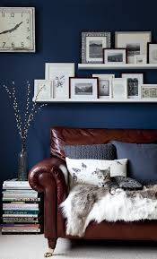 home office dark blue gallery wall. rich brown leather sofa in front of a navy accent wall home office dark blue gallery