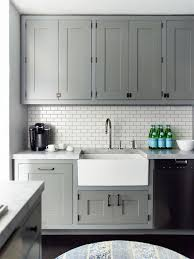 the dark grout on the tiled backsplash complements the cabinets