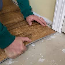 bending a piece of vinyl plank flooring to slip under door jamb in installation process