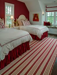 luxurious traditional bedroom white walls collection of striped rug paired two beds paired wall sconces with red bed skirt wood floor
