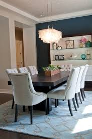 eight off white tufted chairs surround a dark wood table in this chic transitional dining room a dark blue accent wall attracts the eye to the built in