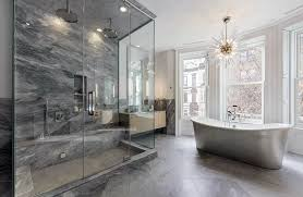 contemporary bathroom with infinity shower drain and freestanding tub with chandelier