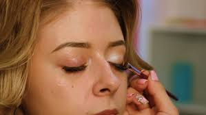 makeup artist apply makeup to the face of the she paints eye shadows