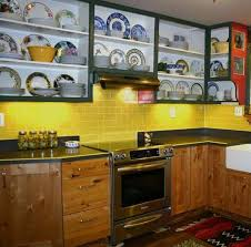 yellow glass subway tile backsplash for kitchen with wooden cabinets and wall mounted open shelving dinnerware