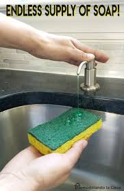 kitchen soap dispenser being pumped onto a green sponge
