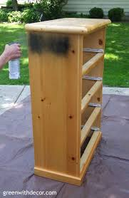 painting a dresser with black spray paint a dresser sitting on a brown tarp