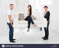 woman office furniture. Full Length Portrait Of Movers Carrying Sofa With Happy Client Woman Sitting - Stock Image Office Furniture