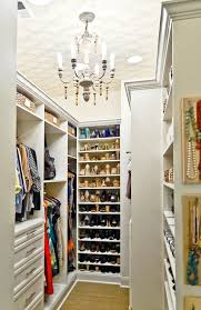 gorgeous closet features wallpapered ceiling punctuated with candle chandelier over wall to wall jute carpeting