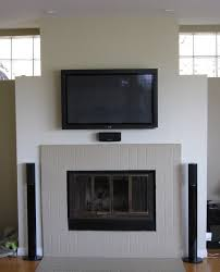 interior white tile fireplace with black metal fire box and lcd tv on white over