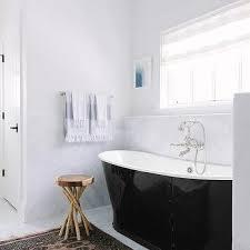 black enameled cast iron bathtub with pink and black rug