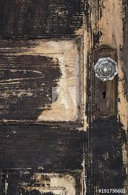 old weathered antique beat up wood panel door with chipped ling paint and glass crystal doorknob and rusted plate