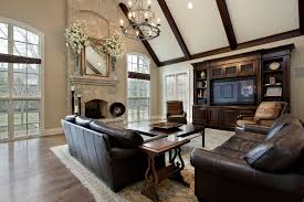 A large living room with a tall light stone fireplace with beautiful  stonework. To the