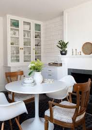 eat in kitchen features an ikea docksta table lined with mid century modern dining chairs and saarinen tulip armchairs placed in front of a white fireplace