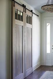foyer boasts dual stained plank shiplap barn doors on rails