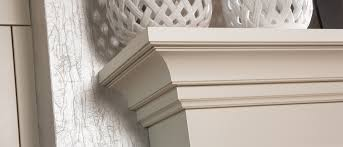 close up of a white fireplace mantel and corbel from dura supreme cabinetry