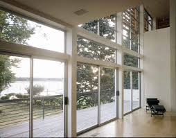 full exterior sliding glass door for modern riverside house design with high ceiling and balcony with stainless steel railings plus hardwood floor tiles