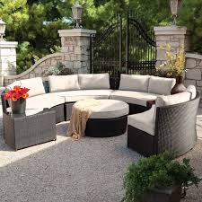 large circular conversation patio sectional features high contrast between dark resin wicker construction and off