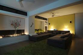 subtle lighting. night view living room with subtle lighting behind the sofa also windows glass covered