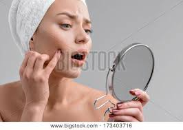 looking in mirror sad. sad young girl is touching her face and looking at mirror with shock in t