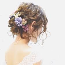 後れ毛がポイントお花を飾ったゆるふわシニヨンの花嫁ヘアが可愛い