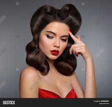 lips makeup and retro curls hair style retro woman looking to the side holds a finger near the head expressive expressions high fashion photo