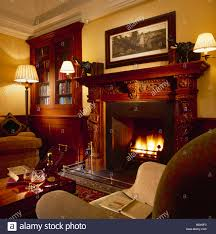 cozy living room with fireplace. Delighful Living Wall Lights On Either Side Of Carved Wooden Fireplace In Cosy Living Room  With Builtin Bookcase With Cozy Living Room Fireplace