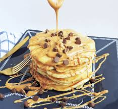 extra fluffy chocolate chip pancakes stacked and topped with a peanut er drizzle and chocolate chips