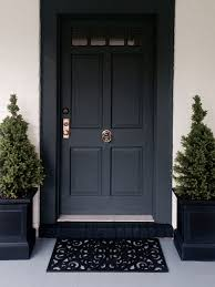 above painting architrave black to match the door will make it appear wider the perfect solution for a narrow door the black planters frame this door and