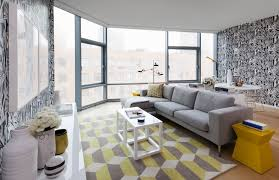 chic yellow gray high rise living room with white black wallpaper accent wall gray sofa with chaise lounge yellow gray geometric rug white parsons chic yellow living room