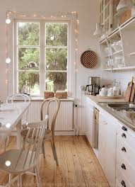 pretty cottage kitchen with a string of lights dd around the window