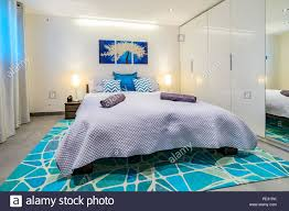 Bedroom Bright Lights Large Bed With Linnens And Bright Blue Pillows In A Modern