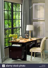 desk in front of window. Simple Front Upholstered Chair At Desk In Front Of Window Corner Room Throughout Desk In Front Of Window E