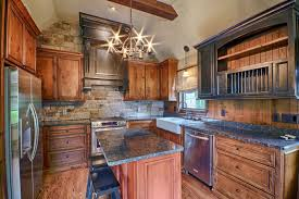 u shaped country kitchen with rustic cabinets steel grey granite countertops and rough cut stone