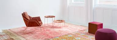 a modern copper colored chair sits atop a warm toned carpet surrounded by two