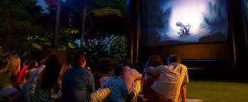 kids watching tv at night. families sitting outside on the grass after dark, watching an animated film a projection. \u0027 kids tv at night