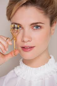 how to use eyelash curler. beautiful woman curling her eyelashes with a curler how to use eyelash