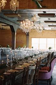reception table decor with chandelier inside rustic barn by jessi pansock photography the pink bride