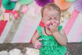 Baby Girl Crying While Eating Birthday Cake During Party Stock