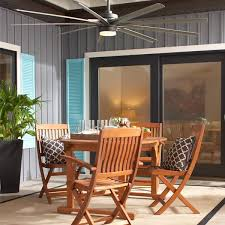 pictured on an outdoor patio above a dining table is a large 9 blade