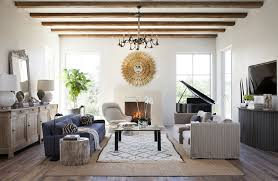 country white house combined with retro interior design set under wooden ceiling beams and decorative chandelier