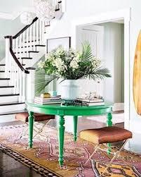 un recibidor muy fresco y elegante una preciosa mesa pintada en verde greenery el
