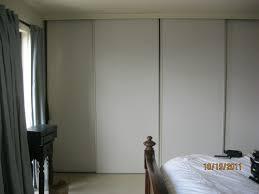 wood sliding closet doors. Furniture. Large White Wooden Sliding Closet Door Connected By Shabby Grey Fabric Curtains On The Wood Doors