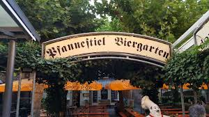is a very traditional german beer garden with wooden tables umbrellas and soccer on the tv
