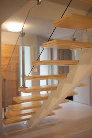 Stainless steel post and glass railings with open wood stair case